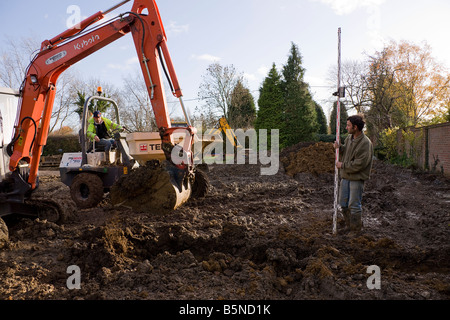 Digging a trench with a digger while preparing the footings. - Stock Photo