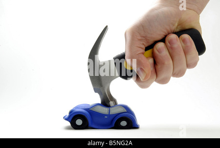 A MODEL CAR HIT AND SQUASHED BY A HAMMER HELD IN A MANS HAND. - Stock Photo