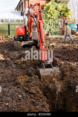 Digging a trench between two piles with a digger. - Stock Photo