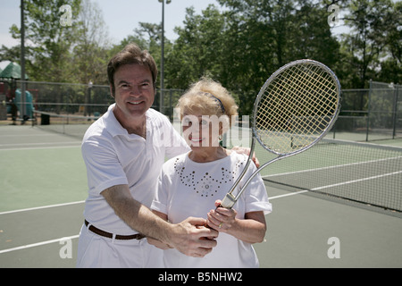 A pretty senior lady on the courts with a tennis pro - Stock Photo