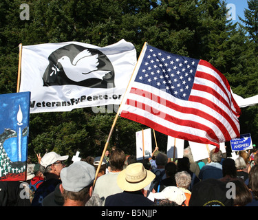 Peace march with USA flag, American flag, at the gates of a US military base, to protest the wars in Iraq and Afghanistan. - Stock Photo