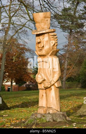 A carving of a tree stump of the Mad Hatter from Alice in Wonderland. - Stock Photo