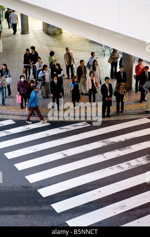 Pedestrians at a crossing in The Shinjuku district of Tokyo, Japan. - Stock Photo