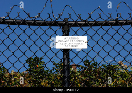 Warning - Private Property - Keep Off Fence - Bad Dog Sign on Fence with Barbed Wire - Stock Photo
