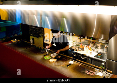 Chef cooking in an Okonomiyaki restaurant in the Shibuya district in Tokyo, Japan. - Stock Photo