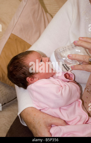 new born 1 Week Old Baby Girl Being Bottle Fed feeding - Stock Photo