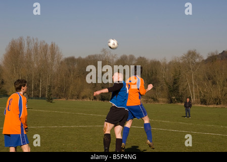 Football Players Heading The Football Soccer Players Jumping For The Ball - Stock Photo
