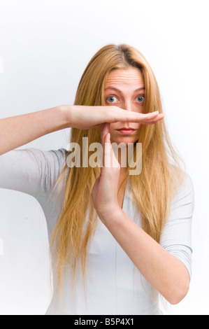young woman with long blonde hair making shape of the T sign for time out with her hands - Stock Photo