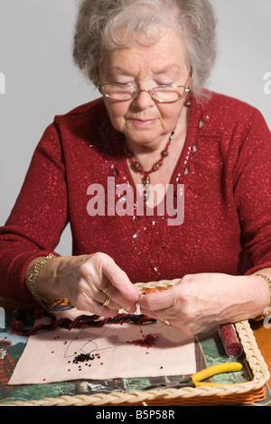 Senior citizen (lady) engaged in her hobby of costume jewellery making using  beads. Shallow DOF with focus on hands. - Stock Photo
