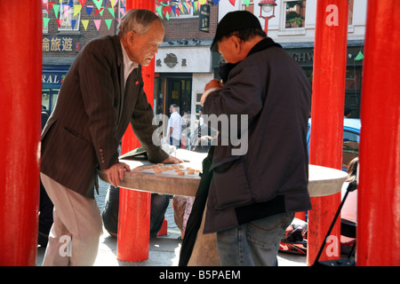 Chinese men play game of draughts in London's Chinatown - Stock Photo