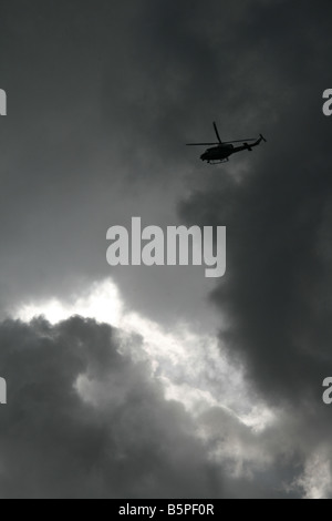one helicopter flying through dark clouds in sky - Stock Photo