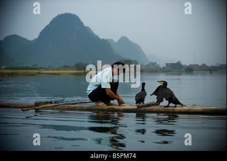 Chinese cormoran fishermen on bamboo raft at evening in Yangshuo, south province of Guangxi - Stock Photo