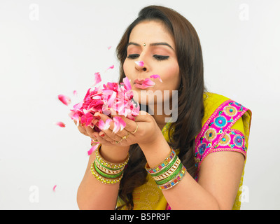 a pretty asian woman blowing rose petals held in her plam - Stock Photo