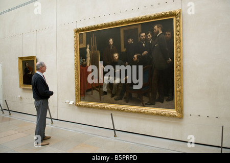 Visitor looking at a painting in Musee d Orsay, Paris France - Stock Photo