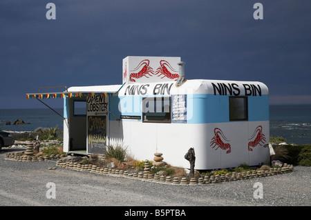 Nins Bin Lobster Caravan and Stormy Sky Kaikoura Coast Marlborough South Island New Zealand - Stock Photo