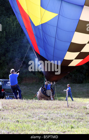 A hot air balloon ready to rise is being held down by two people and anchored for safety - Stock Photo
