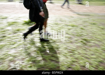 two people walking on muddy path in rural field - Stock Photo