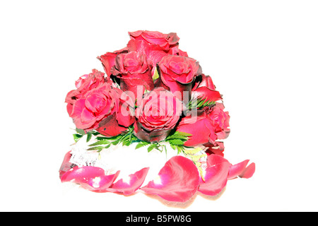 A fancy wedding cake with red roses on top displayed for a wedding reception - Stock Photo