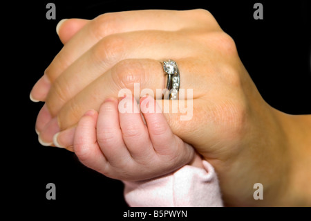 Horizontal studio close up of a newborn baby's hand holding onto a woman's little finger against a black background. - Stock Photo