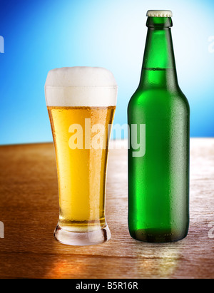 Glass with beer and bottle stand on a table on a blue background - Stock Photo