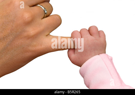 Horizontal studio close up of a newborn baby's hand holding onto a woman's little finger against a white background - Stock Photo
