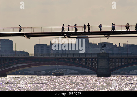 Pedestrians on the Millennium bridge crossing the river Thames. London, England - Stock Photo