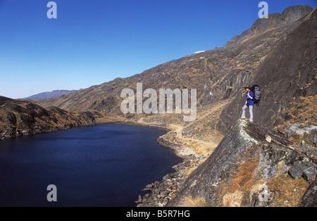 Trekker looking at view over glacial lake on the Takesi Inca Trail, Cordillera Real, Bolivia - Stock Photo
