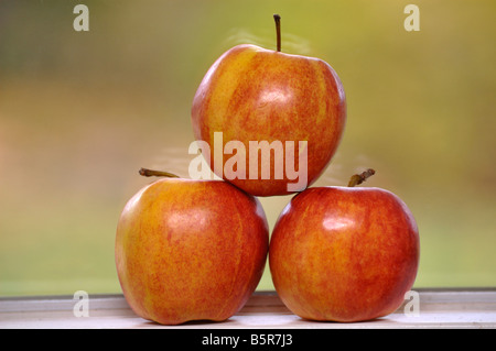 Three apples stacked on a window sill - Stock Photo