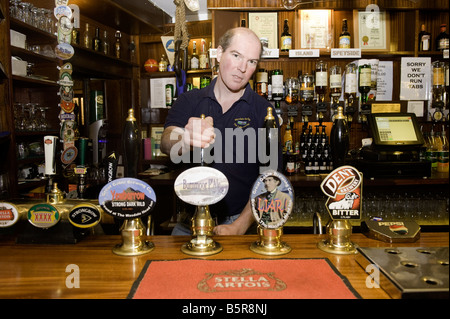 Bar man pulling pints of beer brewed by the pub Wasdale Head Inn Cumbria - Stock Photo