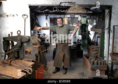 Blacksmith Bruce Wilcock at work in his Forge - Stock Photo