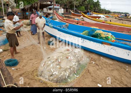 Fishermen sorting their catch on Kalapet beach near Pondicherry India. - Stock Photo