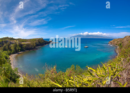 Sailboats and snorkelers in Honolua Bay, Maui, Hawaii. The eastern end of the island of Molokai is in the background. - Stock Photo