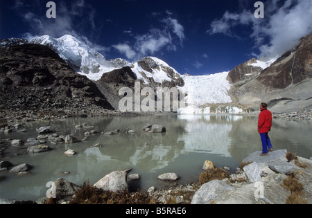 Trekker looking at view at Laguna Glaciar, Mount Illampu in background, Cordillera Real, Bolivia - Stock Photo