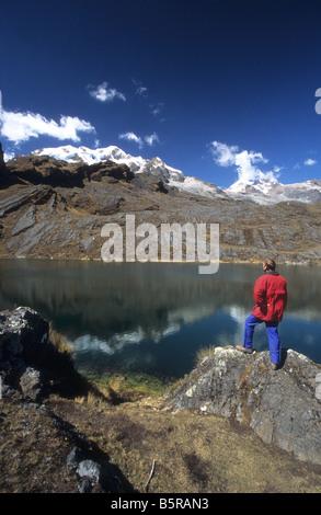 Trekker looking at view across Lake Chillata, Mts Illampu and Ancohuma in background, Cordillera Real, Bolivia - Stock Photo