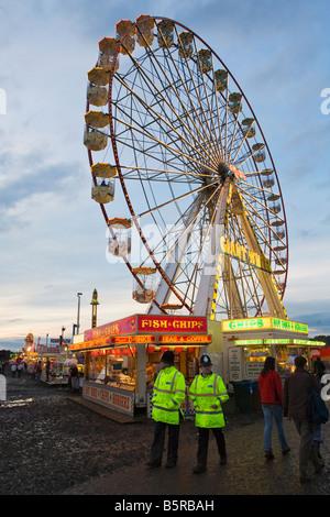 Policemen walking past a ferris wheel at a fun fair at night
