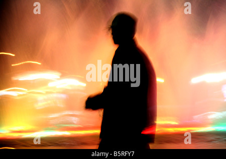 blurry image of a man walking by the light - Stock Photo