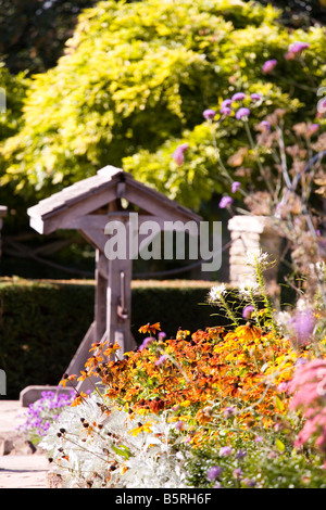 wishing well in a country garden in full bloom - Stock Photo