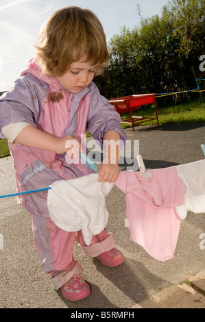 young children in nursery day care centre little girl hanging out clothes to dry on low clothes line - Stock Photo