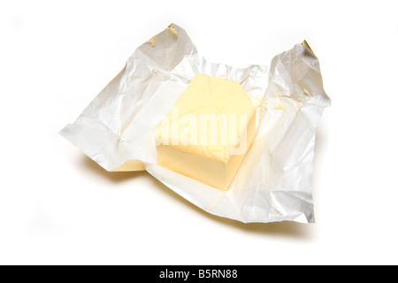 Slab of butter and foil wrapper isolated on a white studio background - Stock Photo