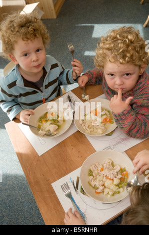 three young  pre school children in nursery day care centre having their midday meal chicken stew, sitting low tables, - Stock Photo