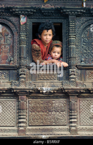Two Tamang girls watch from a window in their elaborately carved wooden house, Gatlang, Tamang Heritage trek, Nepal - Stock Photo
