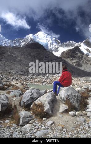 Male trekker looking at view at Laguna Glaciar, Mount Illampu in background, Cordillera Real, Bolivia - Stock Photo