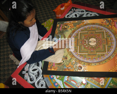 A young women meticulously working on a Thanka in a workshop in Bhaktapur (aka Bhadgaon and Khwopa), Kathmandu valley, - Stock Photo