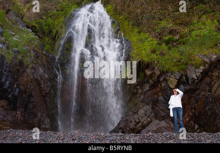 Woman looking out to sea at waterfall on the beach near the coastal village of Clovelly North Devon England UK - Stock Photo