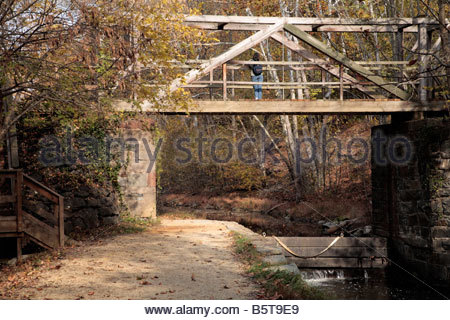 A hiker pauses on the footbridge near the C&O Canal Lock 16 in Maryland. - Stock Photo