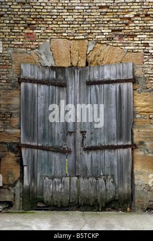 An old derelict wooden door set in weathered brick wall - Stock Photo