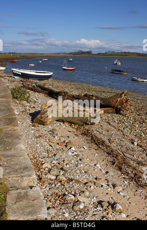 Old quayside at Sunderland Point with boats hauled up in background - Stock Photo