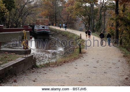 Hikers and runners pass by Locks 19 and 20 on the C&O Canal in Maryland. - Stock Photo