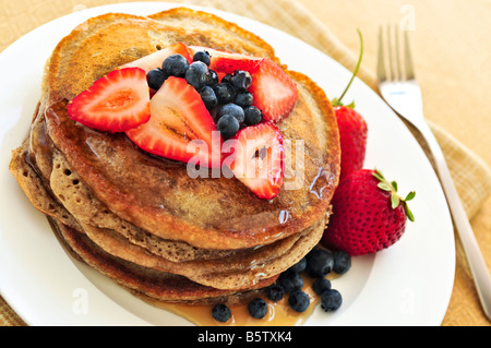 Stack of buckwheat pancakes with fresh berries and maple syrup - Stock Photo
