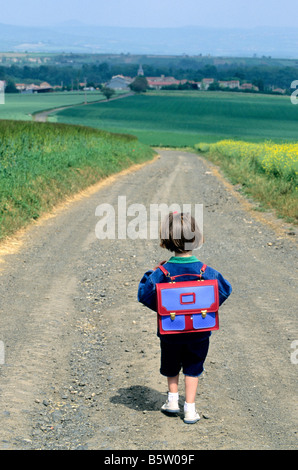 Little girl walking along a country road going to the village school in the countryside - Stock Photo